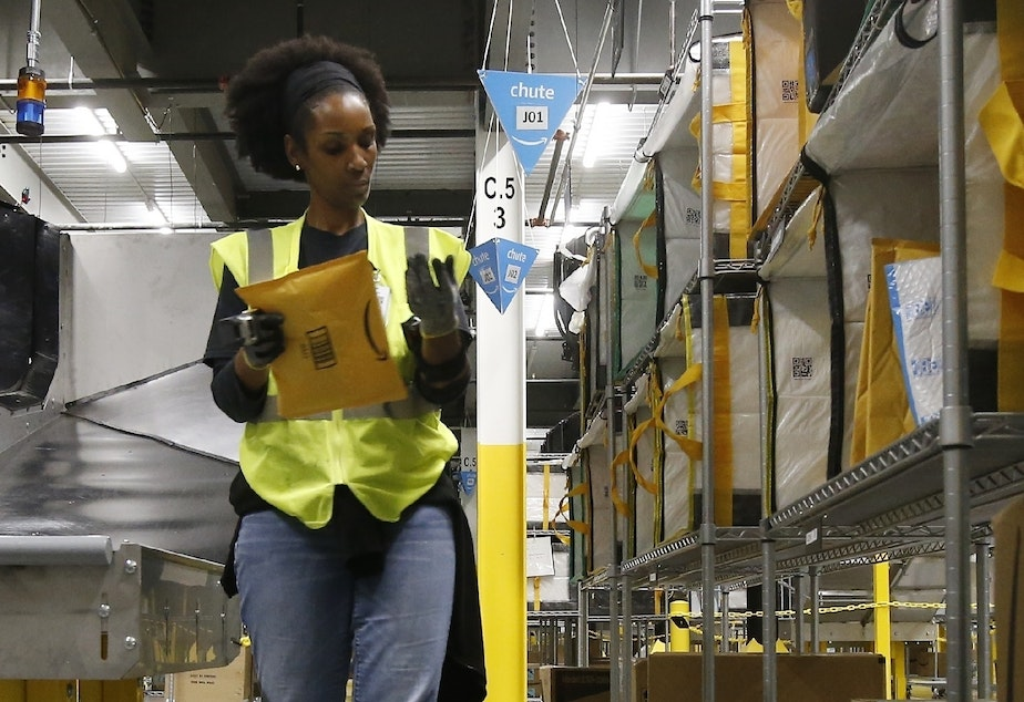caption: An Amazon worker stows packages into special containers at a facility in Arizona. Coronavirus cases have been reported in at least 7 Amazon facilities.