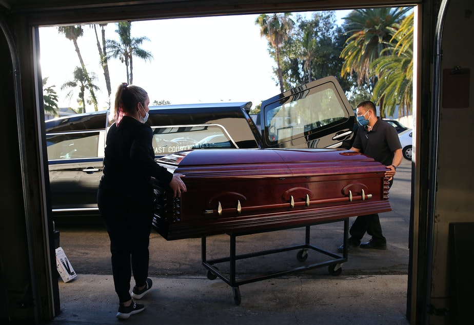 caption: Embalmer and funeral director Kristy Oliver (left) and funeral attendant Sam Deras load the casket of a person who died after contracting COVID-19 into a hearse in El Cajon, Calif. People who work in hospitals and in funeral homes are witnesses to the loss than many Americans can avoid.