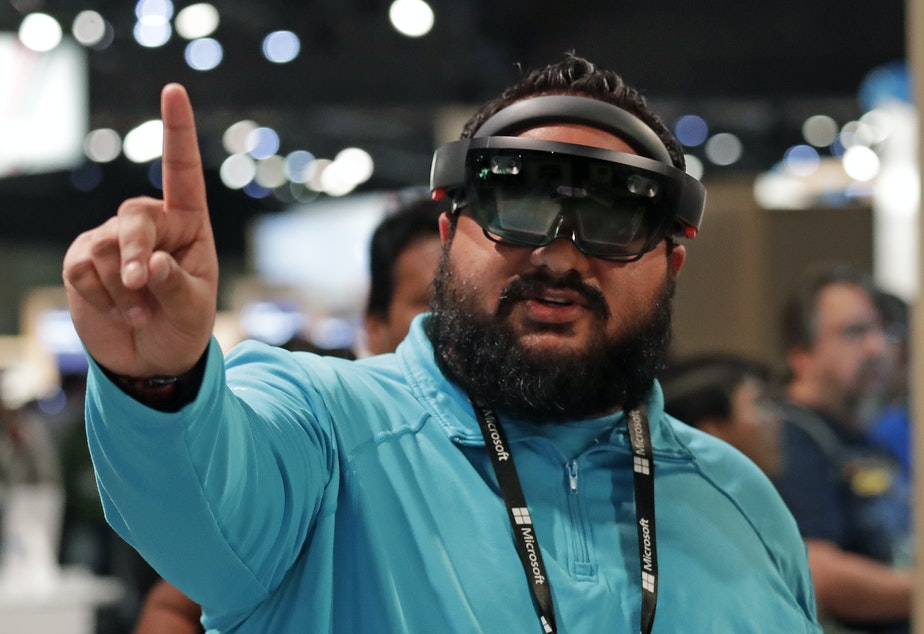 Raman Ghuman demonstrates a HoloLens device at the company's annual conference for software developers, May 7, 2018, in Seattle. Microsoft workers are protesting the use of the HoloLens technology in a U.S. Amy contract.