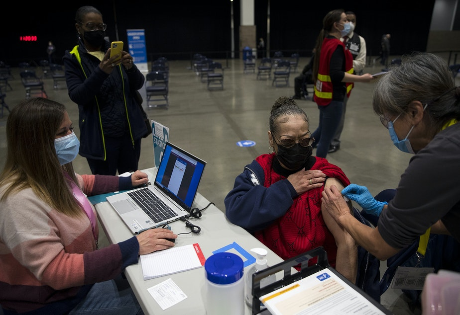 caption: Susan Hughes receives a Covid-19 vaccine at the new civilian-led mass Covid-19 vaccination site on Saturday, March 13, 2021, at Lumen Field Event Center in Seattle.