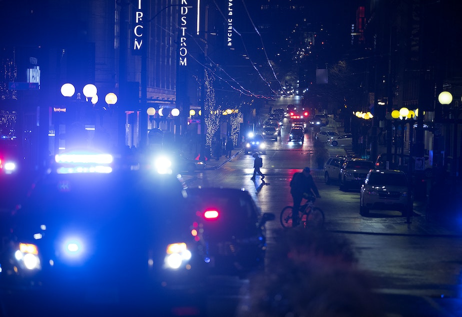 caption: Patrol cars and ambulances are shown at the intersection of Third Avenue and Pine Street on Wednesday, January 22, 2020, following a shooting that left multiple victims injured and one dead in Seattle.