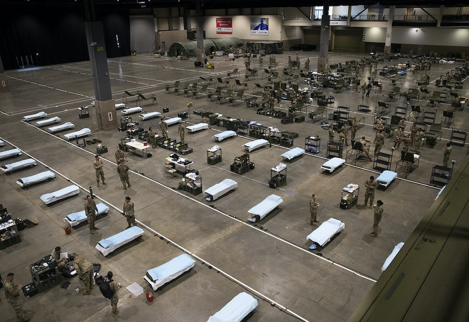 caption: U.S. Army soldiers from the 627th Army Hospital from Fort Carson, Colorado, as well as from Joint Base Lewis-McChord set up a 250-bed military field hospital for non COVID-19 patients on Tuesday, March 31, 2020, at the CenturyLink Field Event Center in Seattle.