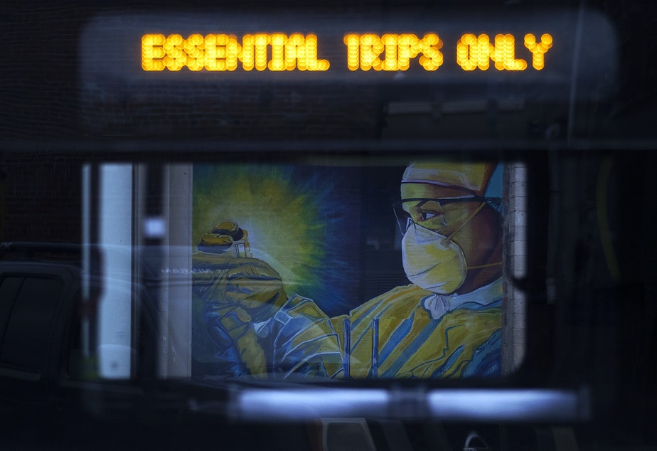 caption: A mural of a healthcare worker wearing personal protective equipment is shown through the window of a passing King County Metro bus on Tuesday, April 28, 2020, along South Main Street in Seattle. As Seattle businesses, coffee shops and restaurants shut down amid the pandemic, plywood replaced their many entrances and windows. Artists transformed that plywood into murals bearing messages of hope and resilience.