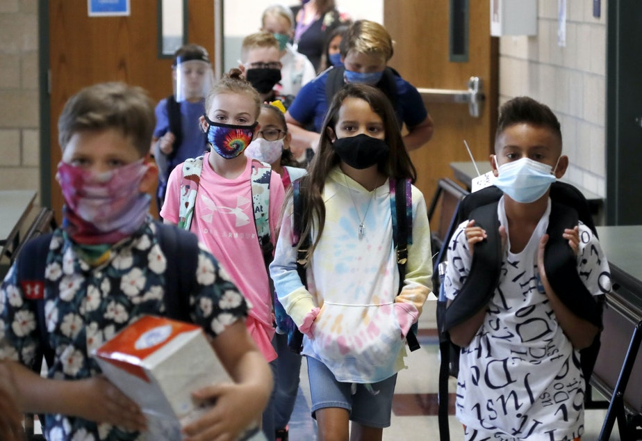 caption: Wearing masks to prevent the spread of COVID19, elementary school students walk to classes to begin their school day in Godley, Texas. (LM Otero/AP)