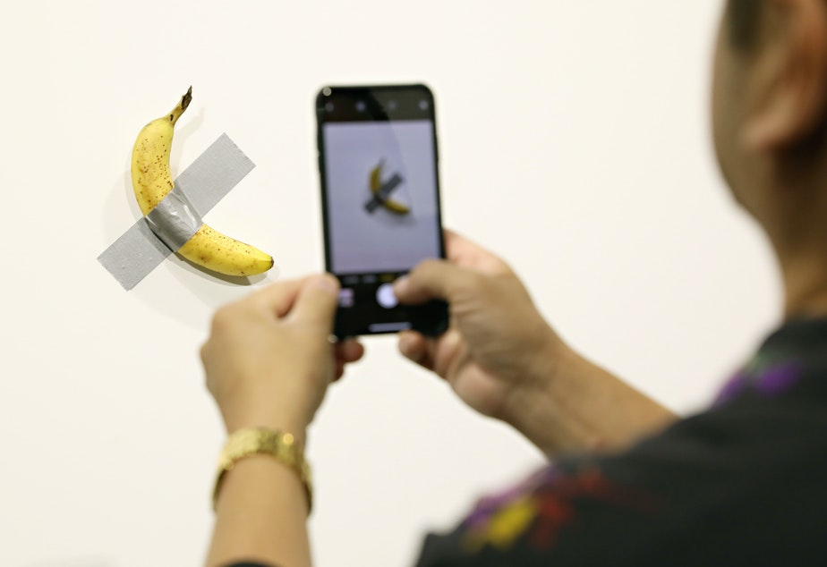 """People view Maurizio Cattelan's """"Comedian"""" on view at Art Basel Miami 2019 Friday. Two of the three editions of the piece, which feature a banana duct-taped to a wall, have reportedly sold for $120,000."""