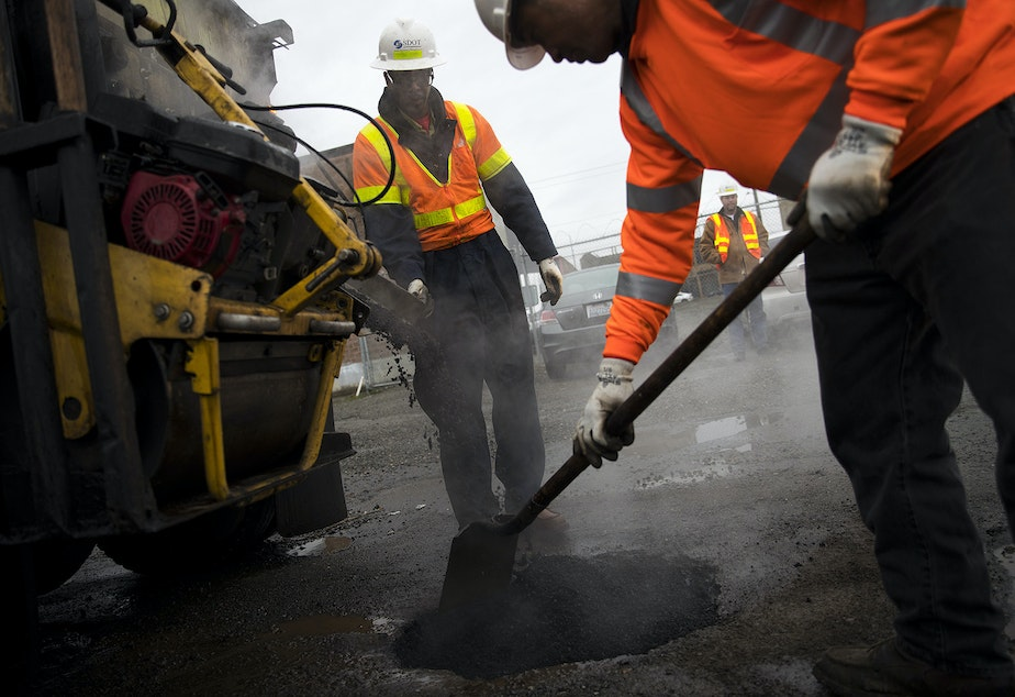Seattle Department of Transportation employees Ben Darrett, left, and Koli Makasini, right, fill a pothole on Tuesday, January 8, 2019, at the intersection of South Forest Street and Occidental Avenue South in Seattle.
