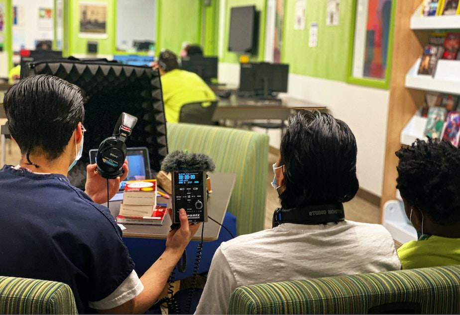 caption: Three teens get ready to record an interview in the library at the Judge Patricia H. Clark Children and Family Justice Center during a RadioActive podcasting workshop on April 15, 2021.