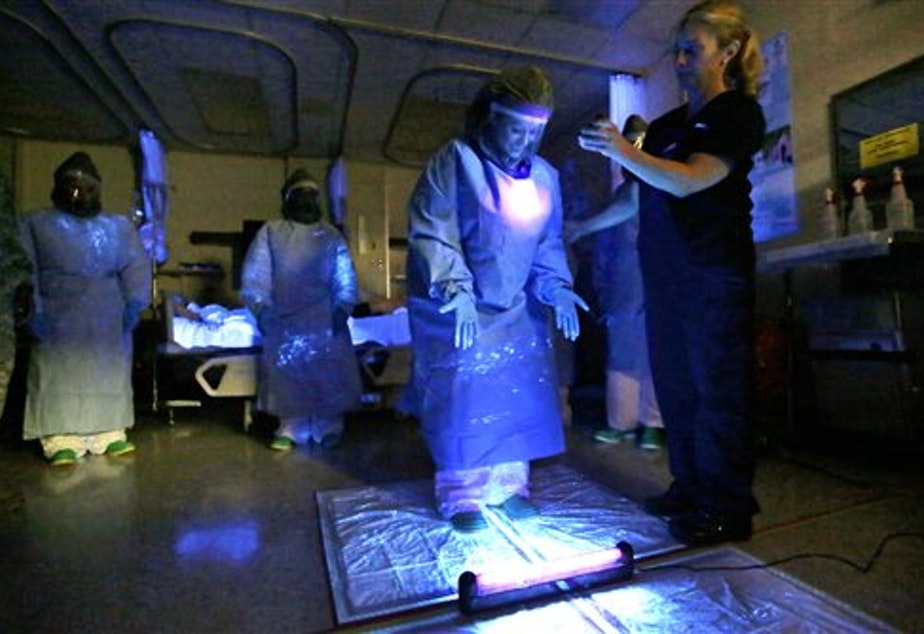 A medical worker, training to treat Ebola patients last week at Madigan Army Medical Center, is illuminated with a black light used to look for traces of fluids which could transmit the Ebola virus.