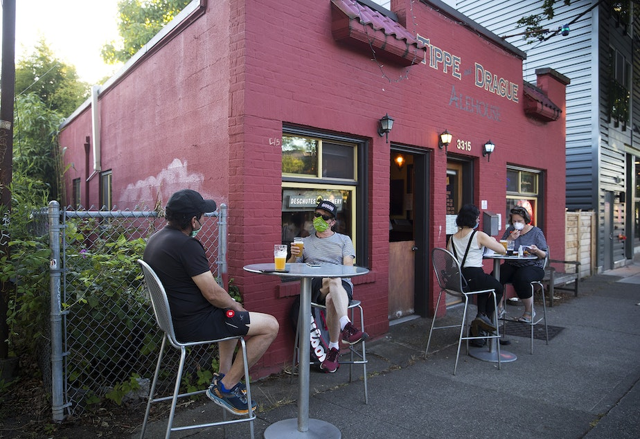 caption: Customers gather outside of the Tippe and Drague Alehouse on Tuesday, July 14, 2020, on Beacon Avenue South in Seattle.