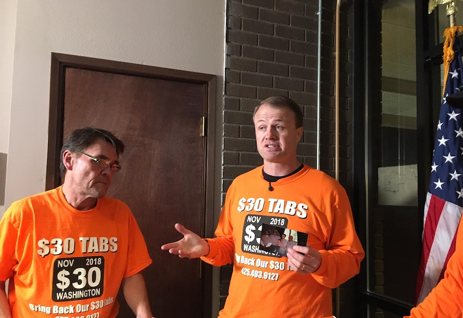 caption: In this file photo from 2018, anti-tax activist Tim Eyman holds a news conference after dropping off petitions for his last car tab reduction ballot measure.