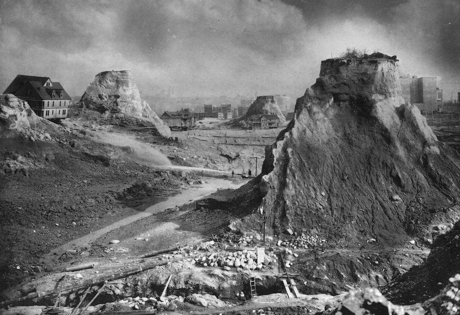 "caption: ""Spite Mounds,"" 1910. The most famous image of the Denny Regrade is often described as depicting ""spite mounds."" But writer David Williams says, at least in one case, it wasn't spite at all that kept these mounds standing. Just paperwork."