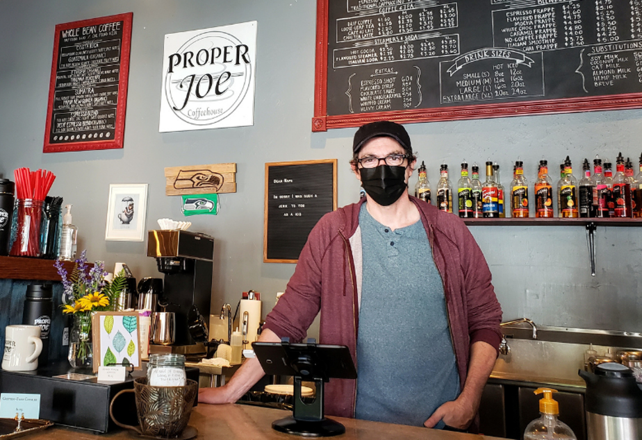 caption: Aaron Donohue offers free masks and hand sanitizer at Proper Joe Coffeehouse in Snohomish on Monday, August 23, 2021.