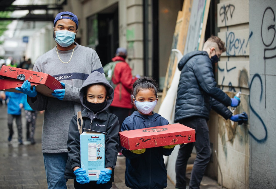 caption: Seattleites, including many families, headed downtown to support the protesters in the form of cleaning up after a hard night of demonstrations.