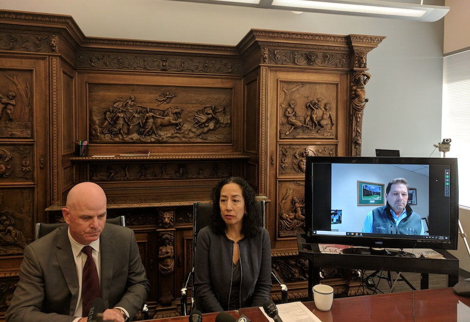 caption: Attorneys Brad Moore, Karen Koehler and John Layman speaking at a press conference. They're bringing a lawsuit against Seattle Children's seeking class action status