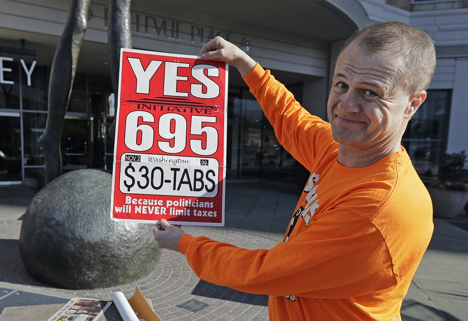 Anti-tax activist Tim Eyman poses for a photo with a sign from his original 1999 campaign for $30 car registration tabs, Tuesday, Nov. 5, 2019, as he waved a sign for his current Initiative 976 on election day in Bellevue, Wash. The measure would again cut most car tabs to $30 in Washington state, if passed by voters, and would leave state and local governments scrambling to pay for road paving and other transportation projects.