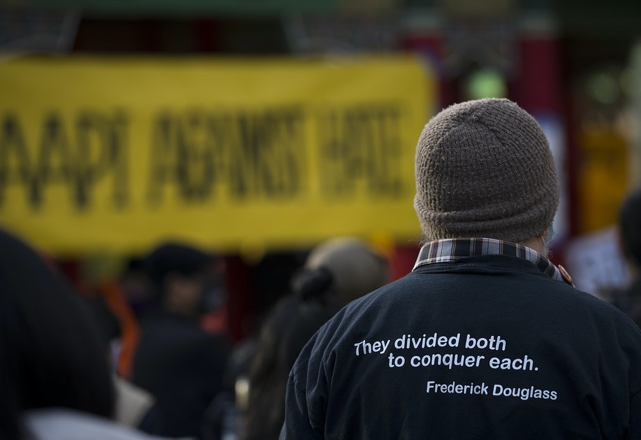 """caption: A person wearing a shirt that includes a quote from Federick Douglass, """"they divided both to conquer each,"""" listens to speakers as hundreds gathered for the 'We Are Not Silent' rally and march against anti-Asian hate and violence on Saturday, March 13, 2021, at Hing Hay Park in Seattle. Several days of actions are planned by rally organizers in the Seattle area following recent attacks and violence against Asian American and Pacific Islander communities."""