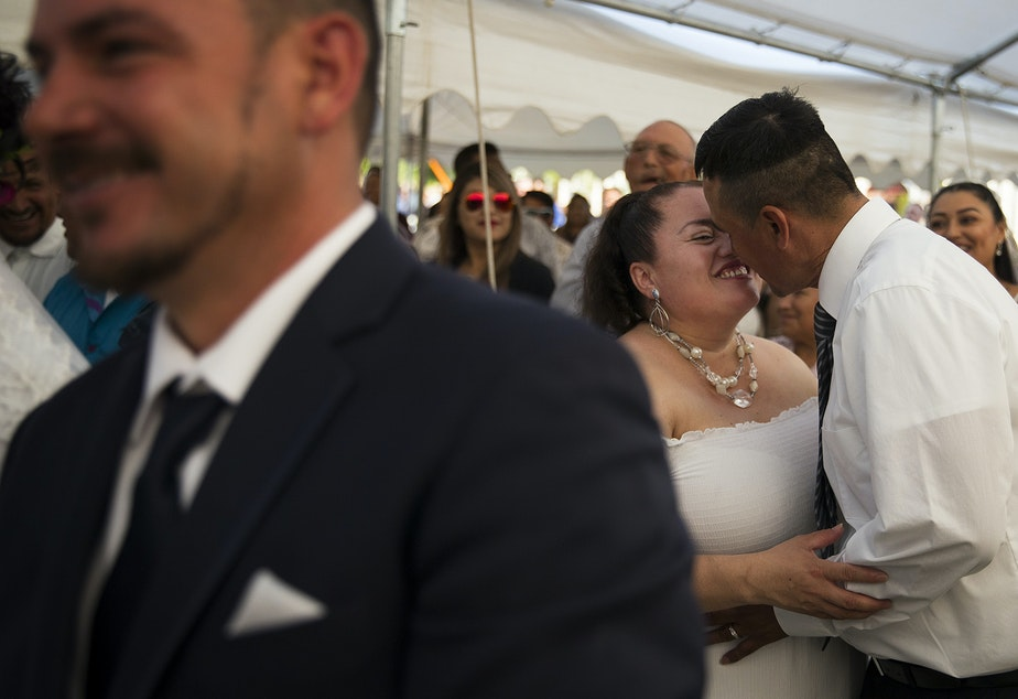 caption: Ana Dely Morales and Ramon Sanchez Cordova share a kiss during a mass wedding ceremony where they were married along with 22 other couples on Sunday, June 2, 2019, at Our Lady of the Desert Church in Mattawa.