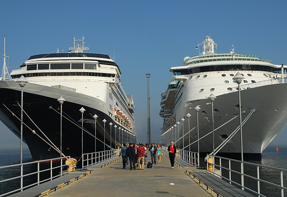 caption: People walking down a pier between two large cruise ships.