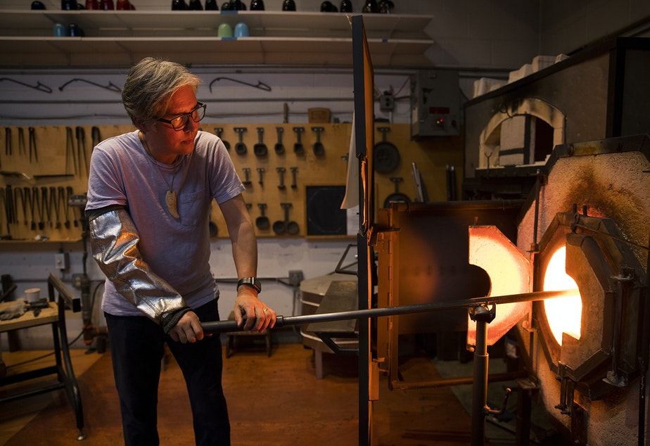 Glass artist Preston Singletary works on sculpting a glass form to later do design work on, on Tuesday, December 11, 2018, at his studio in Seattle.
