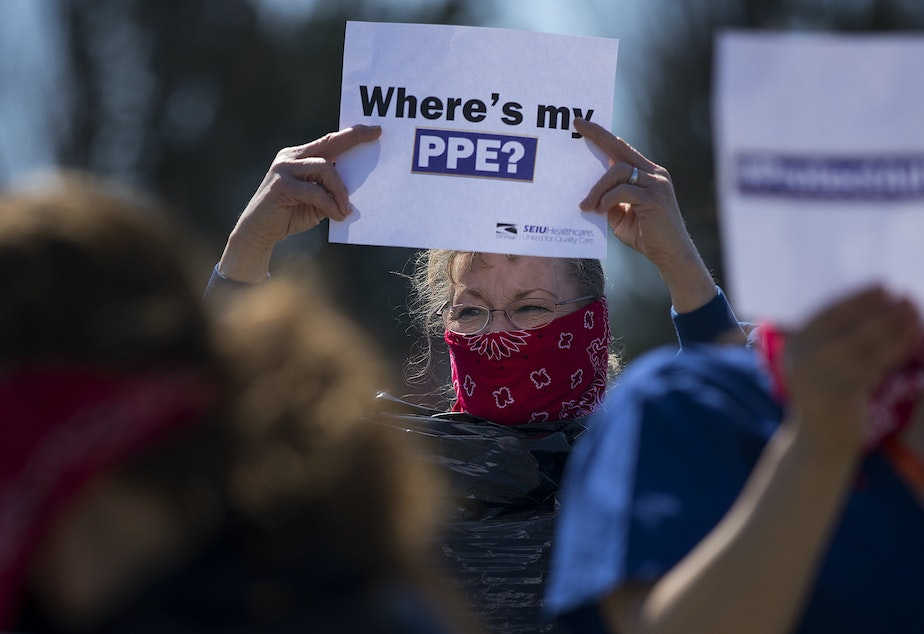 caption: Cindy Hill wears a garbage bag and handkerchief while joining a nationwide protest demanding PPE for healthcare workers on Thursday, April 9, 2020, outside of Evergreen Health in Monroe.