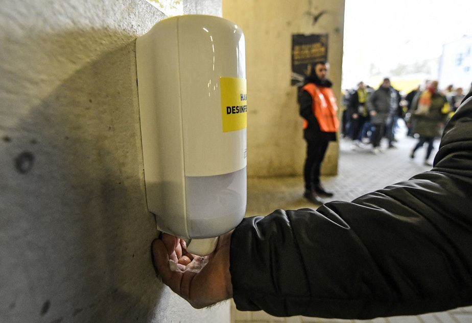 caption: A fan washes his hands at a new disinfection station in the stadium because of the COVID-19 coronavirus outbreak in Germany prior the German Bundesliga soccer match between Borussia Dortmund and SC Freiburg in Dortmund, Germany, Saturday, Feb. 29, 2020.