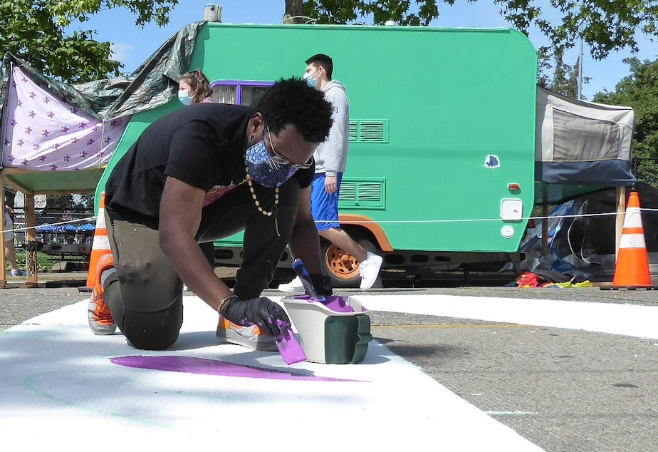 "caption: Moses Sun paints in the ""M"" letter in the BLACK LIVES MATTER letters along Pine Street in Seattle."
