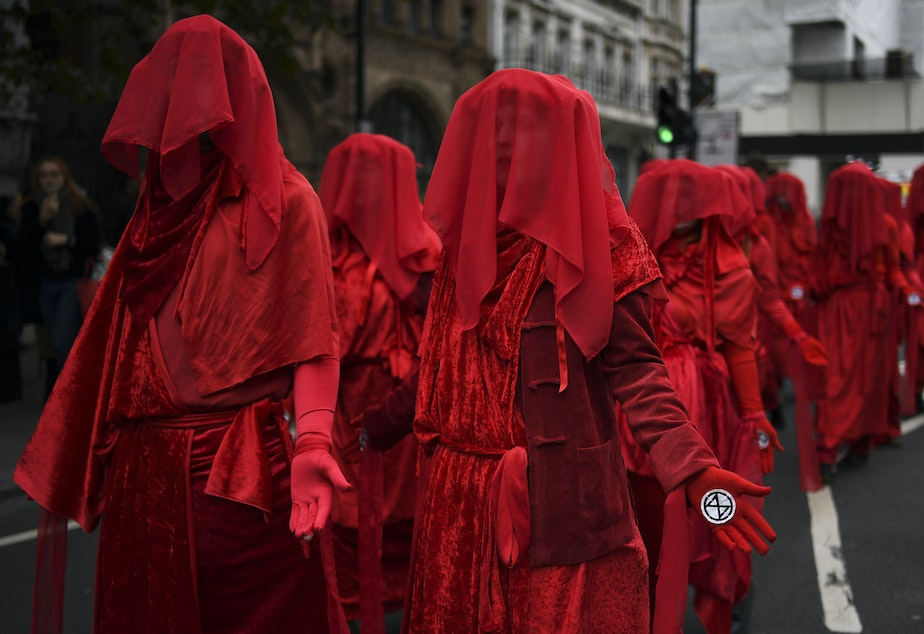 caption: Climate activists take part in a demonstration Monday in London, where police say they've arrested dozens of protesters as the Extinction Rebellion group attempts to draw attention to climate change.