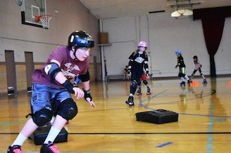 Members of the Wheat Whackers junior roller derby league in Pullman, Wash., as they practice rollerskating maneuvers. CREDIT: AFIQ HISHAM
