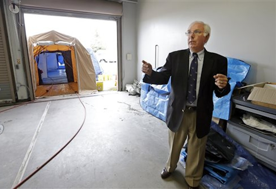 caption: Dennis Peterson, Snohomish County Medical Examiner's office deputy director, talks about the tented area behind him used for decontaminating bodies just outside an intake area at the office.