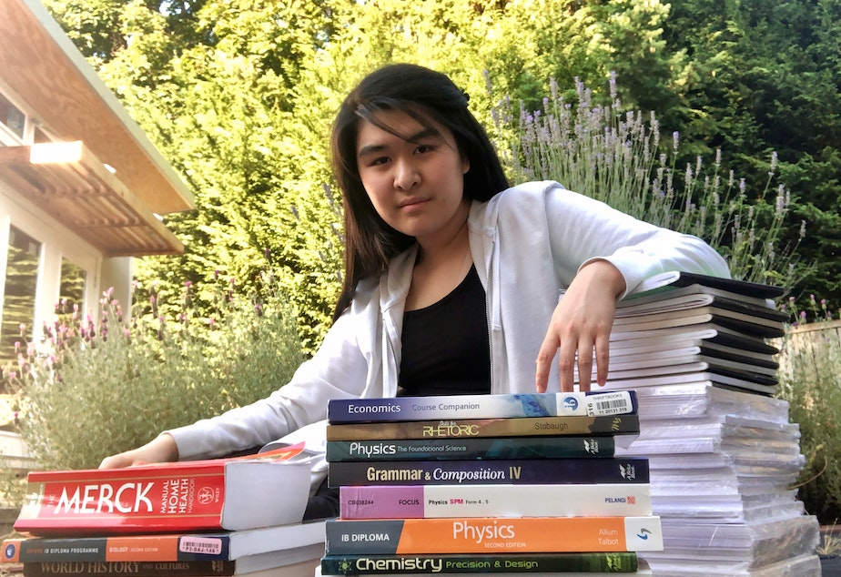 caption: The school records that Lisa Chua kept (saran-wrapped, bottom of right stack) got Emily Chua into college. Also pictured are some of the textbooks and notebooks that got Emily through high school.