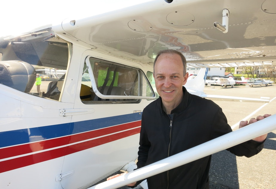 caption: Boeing test pilot, Troy Larson, poses for a photo before flying boxes of surgical masks to rural hospitals in Northeastern Washington.