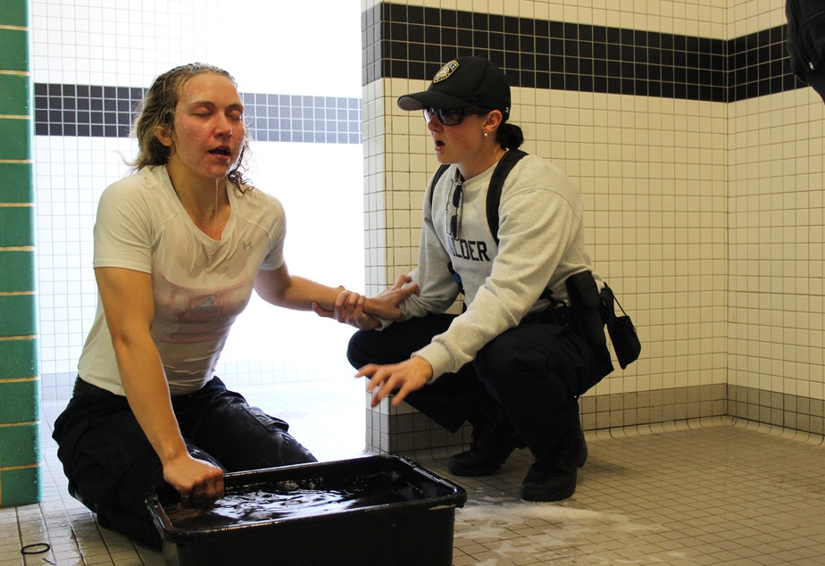 caption: Stephanie Schendel, 25, decided to become a police officer after reporting on crime and courts. The week before graduating from police academy, she was pepper-sprayed during training. Recruit Melissa Calder, a former Lamaze coach, helps her breathe.