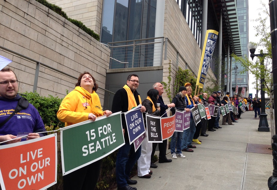 caption: Demonstrators in Seattle form a human chain around City Hall in support of a $15 minimum wage in April 2014.