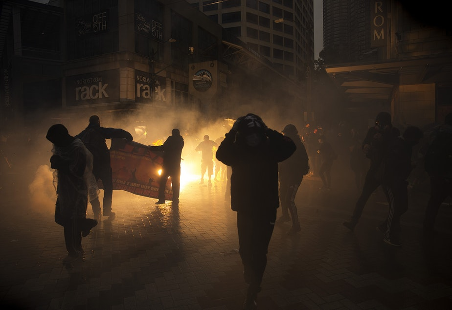 caption: Protesters scatter as a flash bomb thrown by Seattle Police explodes on Saturday, May 30, 2020, at the intersection of 5th and Pine Streets in Seattle. Thousands gathered in a protest following the violent police killing of George Floyd, a black man who was killed by a white police officer who held his knee on Floyd's neck for 8 minutes and 46 seconds, as he repeatedly said, 'I can't breathe,' in Minneapolis on Memorial Day.