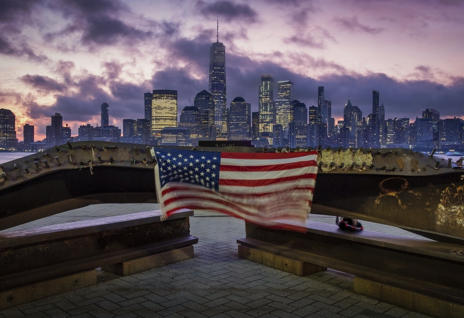 A U.S. Flag hanging from a steal girder, damaged in the Sept. 11, 2001 attacks on the World Trade Center, blows in the breeze at a memorial in Jersey City, N.J., Sept. 11, 2019 as the sun rises behind the One World Trade Center building and the re-developed area where the Twin Towers of World Trade Center once stood in New York City on the 18th anniversary of the attacks.