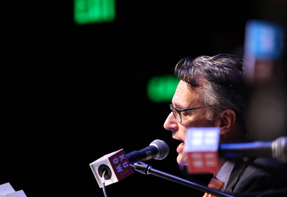 caption: KUOW's host of The Record and Week in Review, Bill Radke, on stage at a live event.