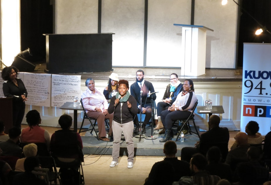 "The panel of guest speakers at ""Black In Seattle"" listen as an audience member adds to the conversation."