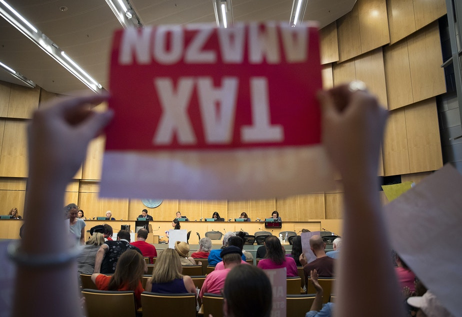 caption: Caitlin Lee raises a Tax Amazon sign in front of Seattle City Council members on Monday, May 14, 2018, during a head tax vote at City Hall in Seattle.