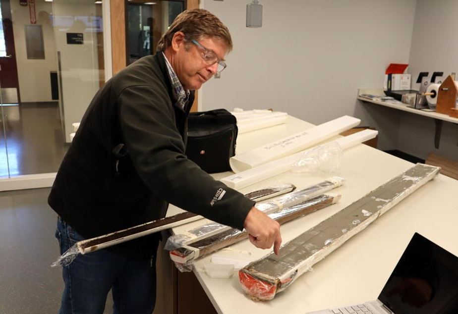 Oregon State University marine geologist Chris Goldfinger shows an offshore sediment core, fat tube on right, and skinnier cores from Pacific Northwest lake bottoms, all of which contain traces of ancient earthquakes.