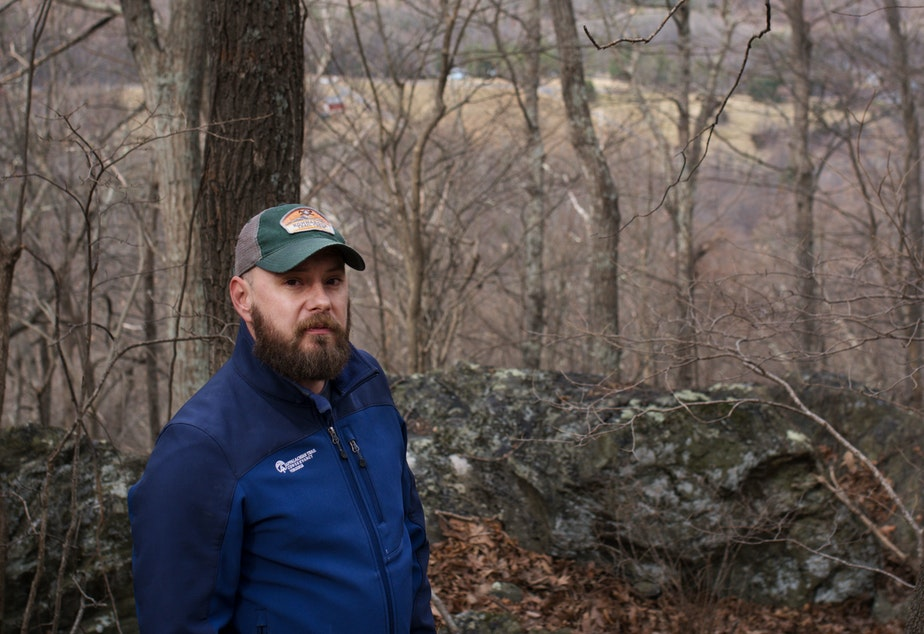 caption: Andrew Downs, senior regional director for the southern region of the Appalachian Trail Conservancy, stands at the approximate spot where the pipeline would cross underground.