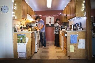 Deborah Bartlett, shown here in her kitchen with Ponch Hartley, cooks meals in her South Lake Union home so she's not tempted to patronize her neighborhod's pricey restaurants.