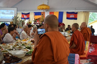 Venerable Prenz Sa-Ngoun snaps photos of a Sunday Buddhist ceremony on his phone. He later posts his photos on Instagram.