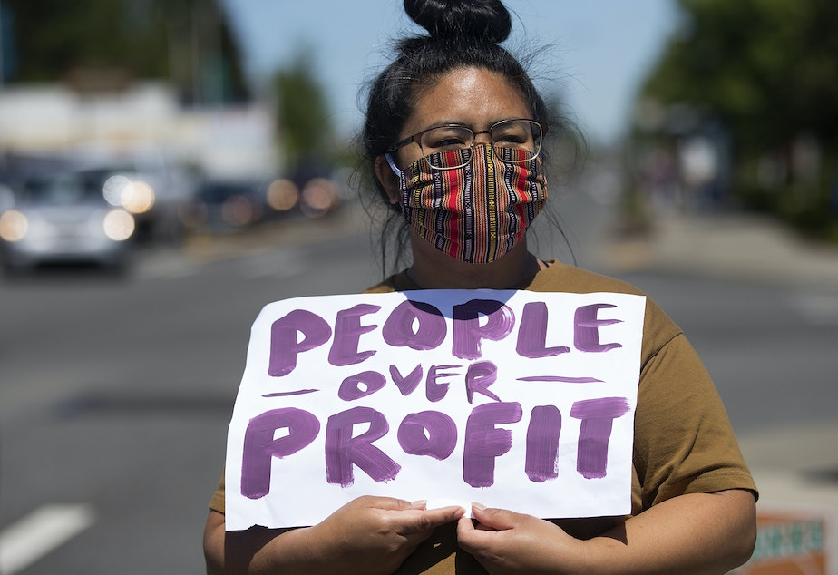 caption: EJ Agoot holds a People over Profit sign while standing in solidarity with essential workers at the Don't Cut Hero Pay rally on Friday, May 15, 2020, outside of Fred Meyer along 1st Avenue South in Seattle.