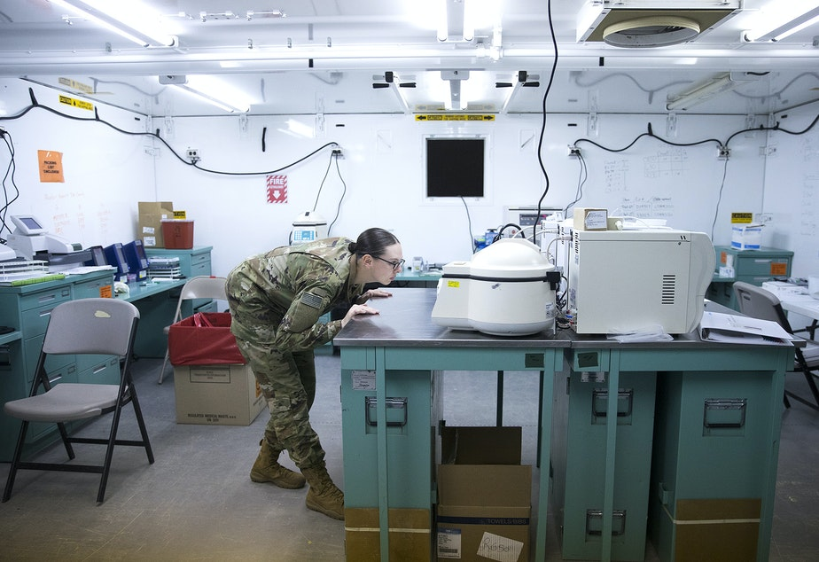 caption: Spc. Ashley Wells, a laboratory technician with the 10th Army Field Hospital, looks into a centrifuge in the laboratory area of the military field hospital inside CenturyLink Field Event Center on Sunday, April 5, 2020, in Seattle. The 250-bed hospital for non COVID-19 patients was deployed by soldiers from the 627th Army Hospital from Fort Carson, Colorado, as well as soldiers from Joint Base Lewis-McChord.