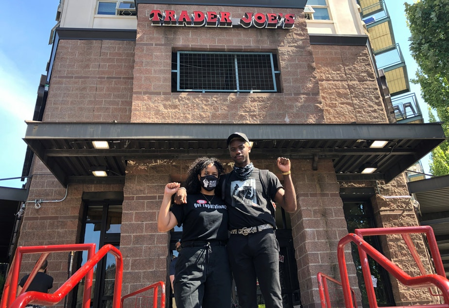 caption: Trader Joe's employees Erin Or (left) and Tre Scott (right) pose for a photo in front of the currently closed Capitol Hill store on Thursday, June 25, 2020.