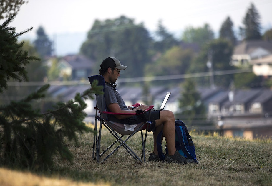 caption: Ben Gilmer works remotely as his children attend theater camp nearby on Friday, August 13, 2021, at Jefferson Park in Seattle.