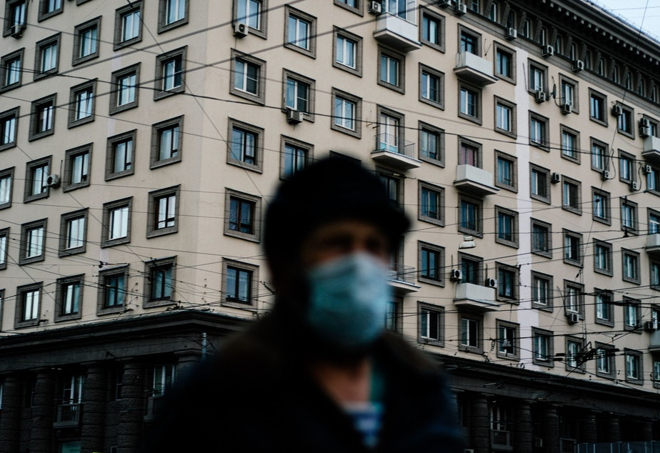 caption: A man wearing a face mask walks in Moscow during a strict lockdown to stop the spread of the coronavirus on April 15, 2020.