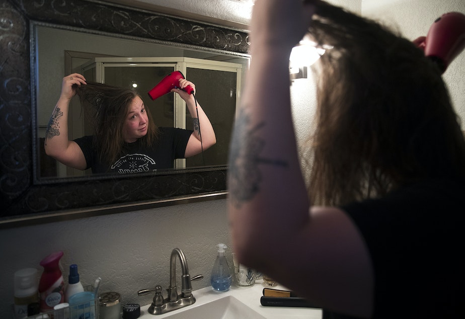 caption: Kara Peters blow dries her hair while getting ready for work on Wednesday, January 22, 2020, at her home in Tacoma. Peters commutes by bus from Tacoma to her job at the Seattle Public Central Library.