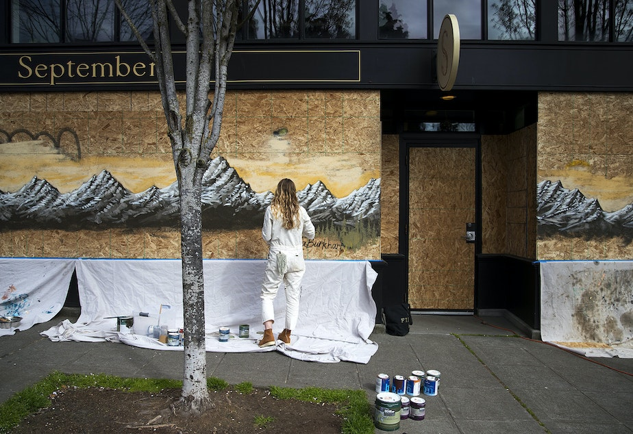 caption: Laura Burkhart paints a mural onto the boarded up facade of September, a clothing store on 22nd Avenue on Sunday, April 5, 2020, in the Ballard neighborhood of Seattle.