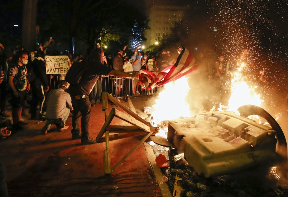 caption: Demonstrators start a fire on Sunday near the White House as they protest the death of George Floyd.